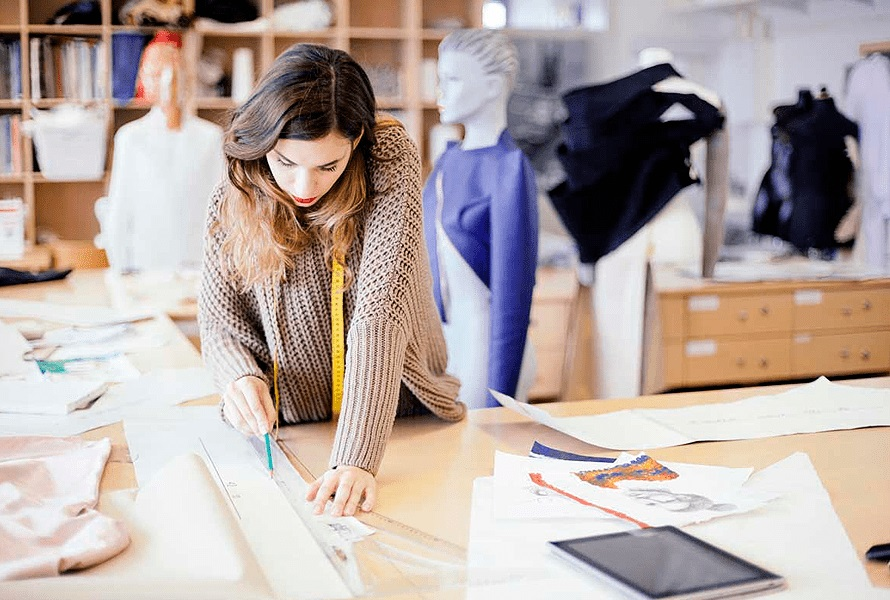 Baplin Uniformes - Mujer trabajando en el diseño y confección de vestuario